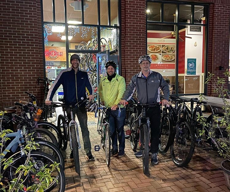 three riders in front of shop