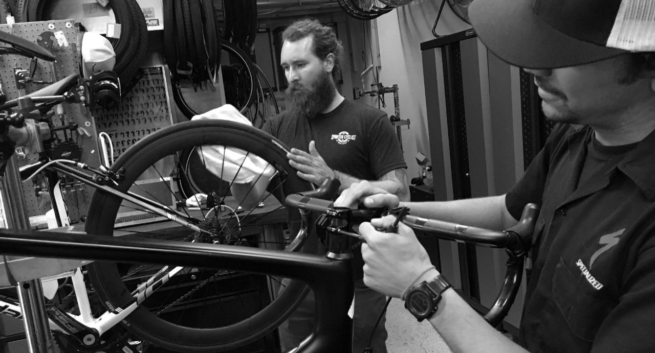 two mechanics working on bikes