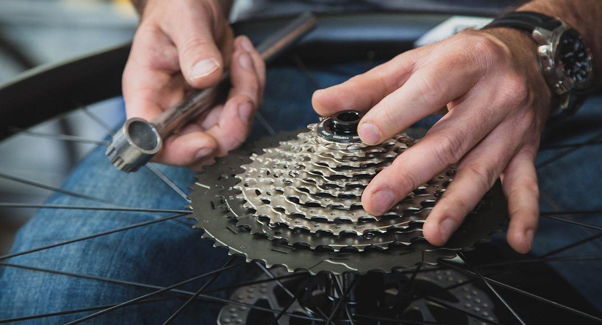 A bike mechanic installs a cassette onto a wheel