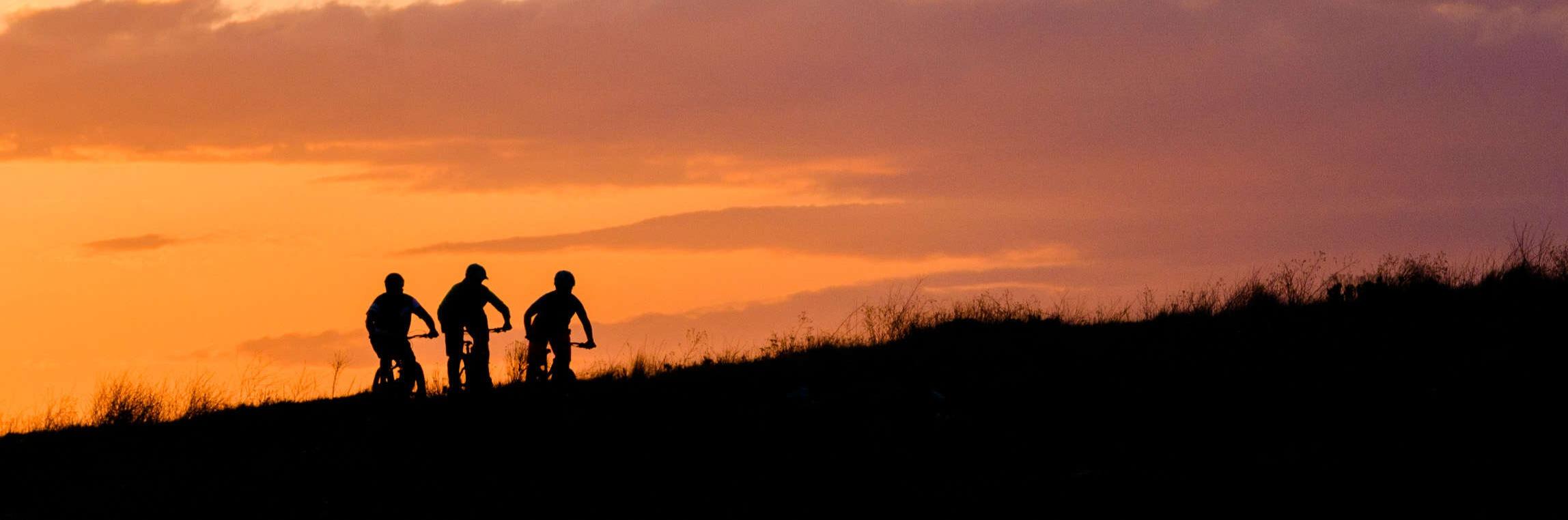 three mountain bikes riding at sunset