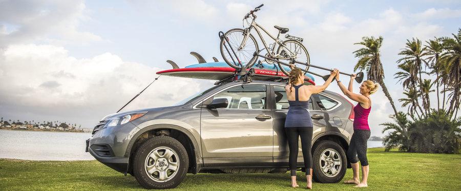 Two women putting a bike onto a car rack.