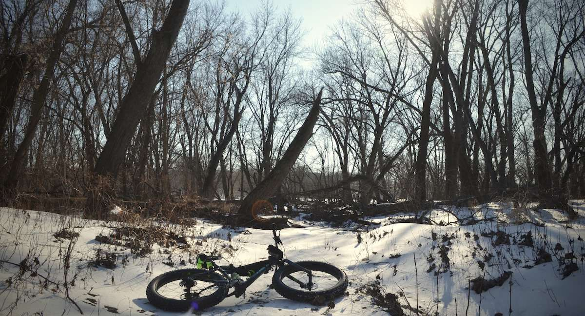 Photo of a fat bike laying across a snowy trail.