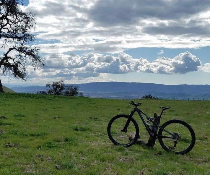 a snapshot of a bike up against a post with a view of the clouds and mountains