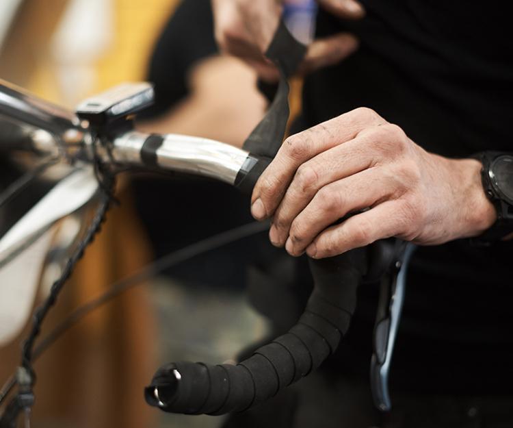 Bike Technician wrapping road bike handlebars with new tape