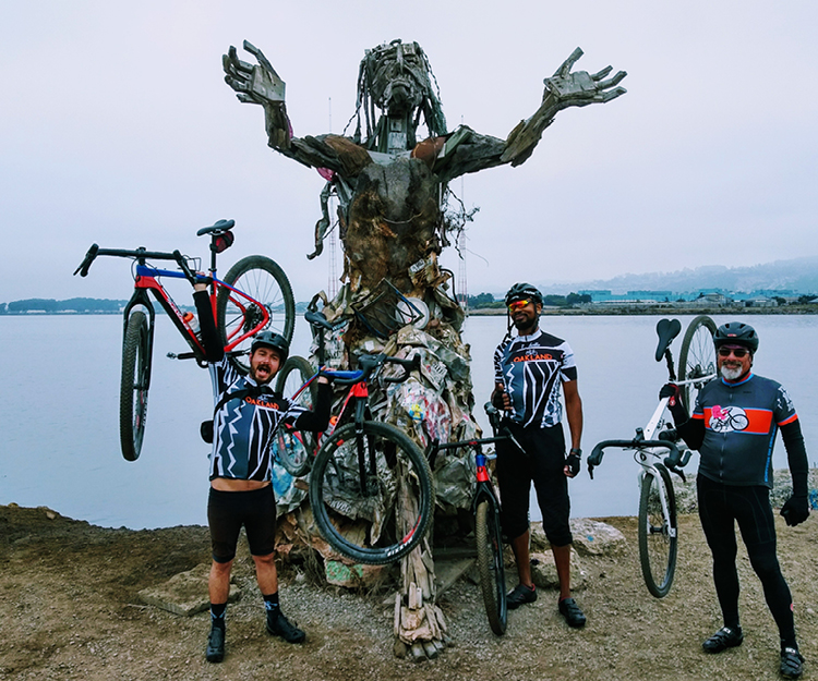 Group of cyclists in front of a sculpture.