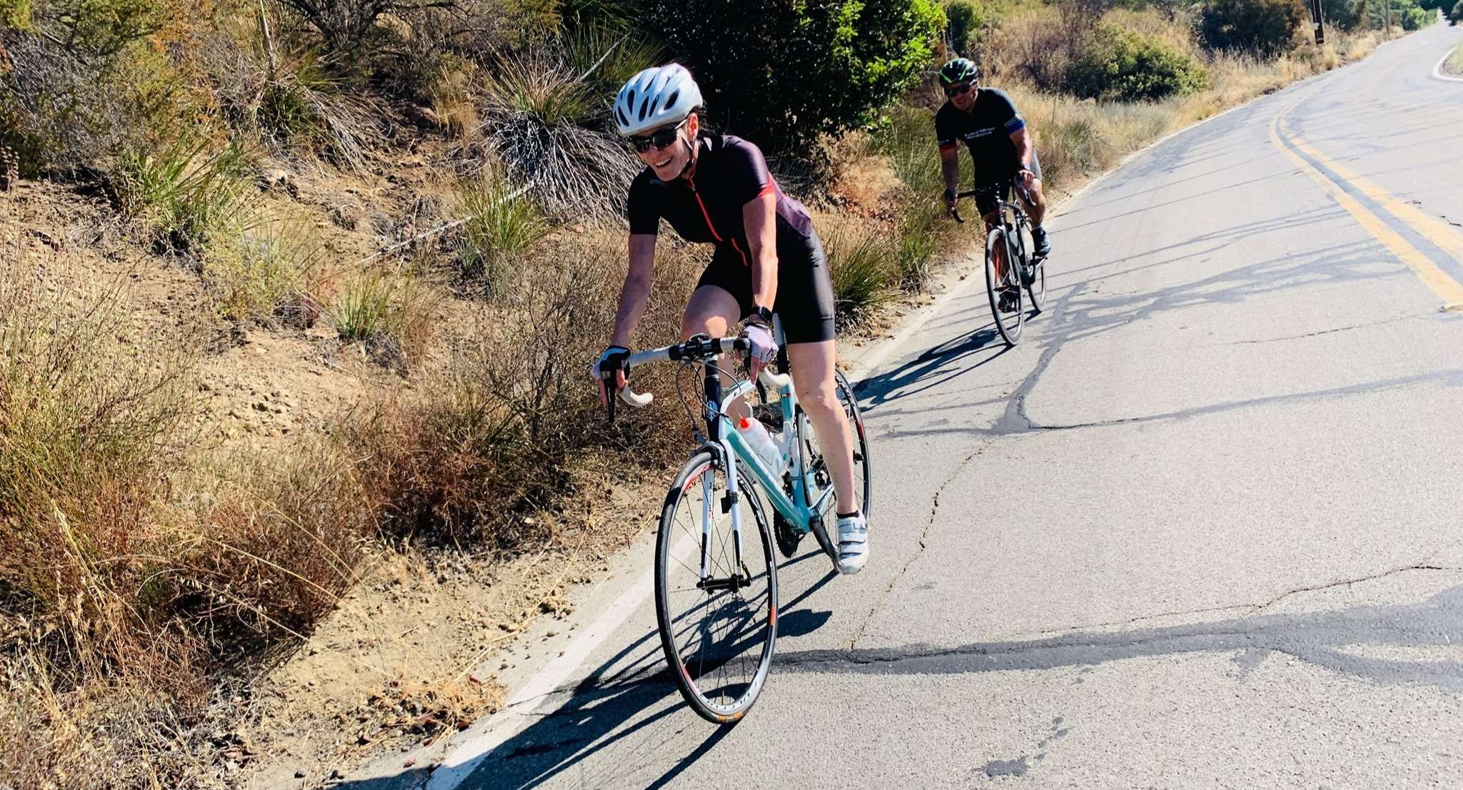 Two cyclists ride on a paved road