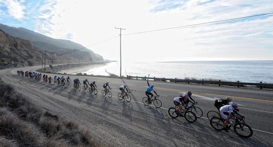 A large group of road cyclists ride a road near the ocean