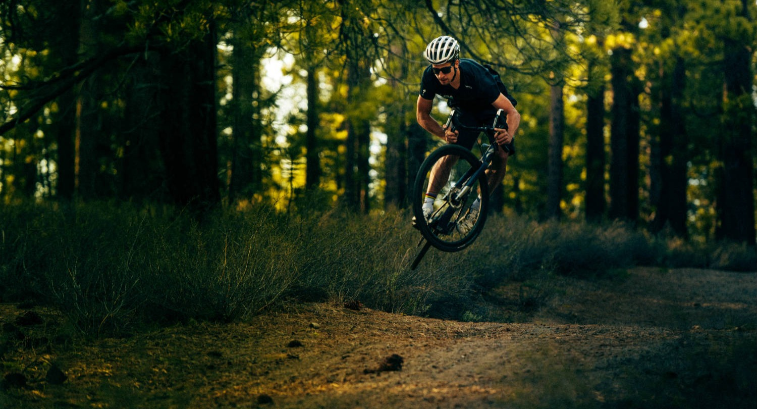 A cyclist jumps his bike on a forest trail