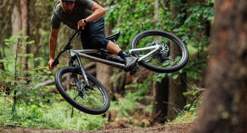 A mountain biker jumps his bike on a forest trail
