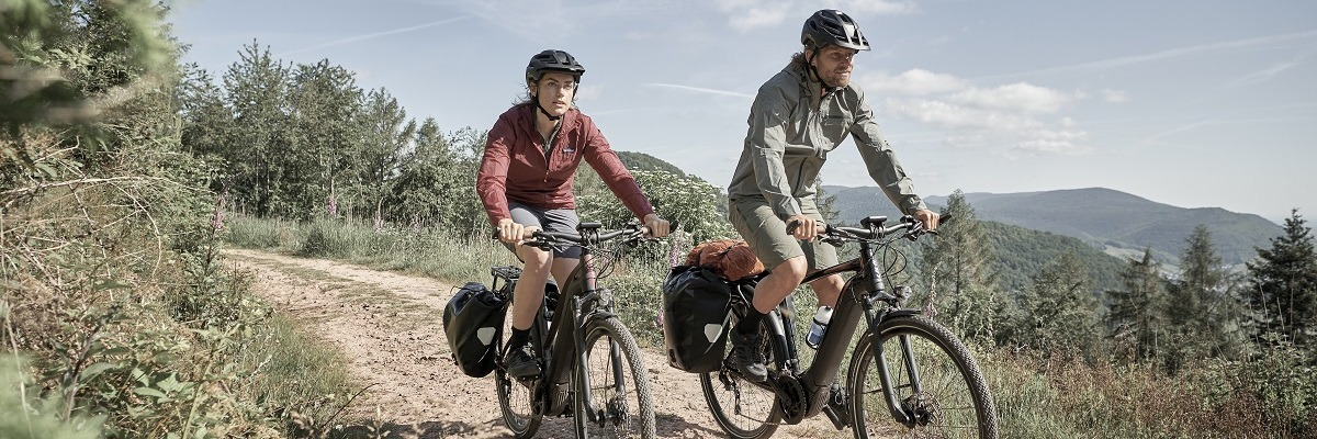 Woman and man riding x-road e-bikes along a dirt and gravel path in the grassy wilderness
