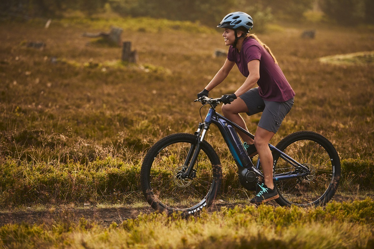 Woman riding Liv Tempt E+ e-mountain bike (hardtail) across a gravel path through a grassy field