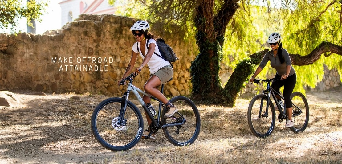 Two women riding offroad on a gravel path on Liv bicycles