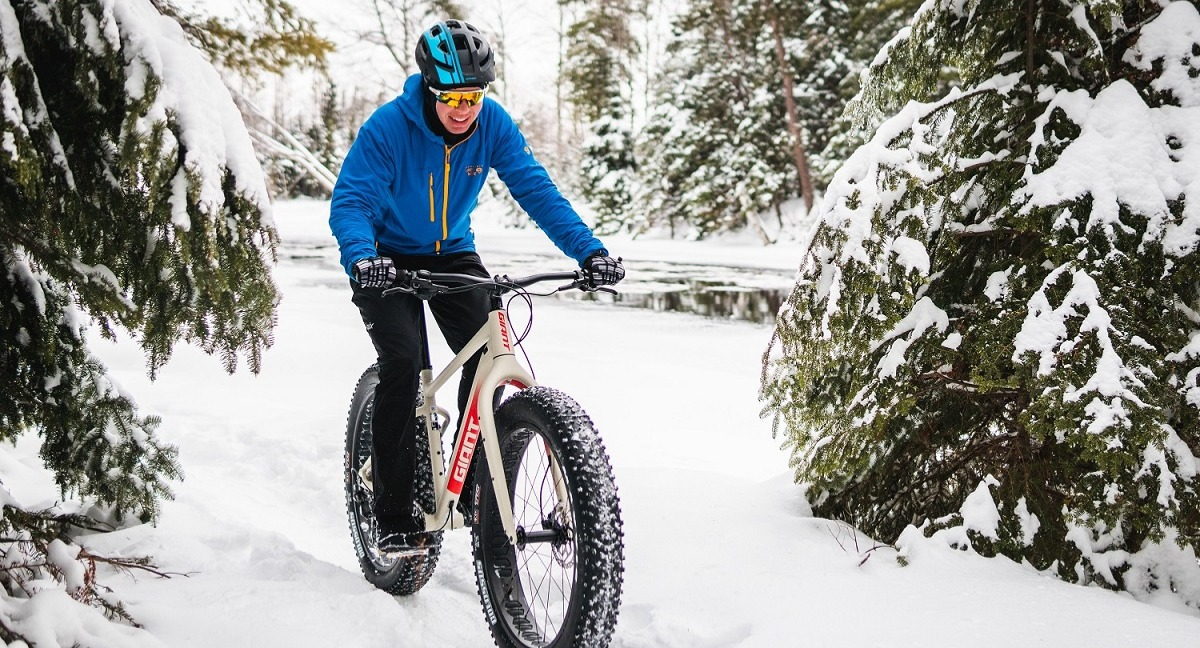 Person riding a Giant fat bike through deep snow in winter