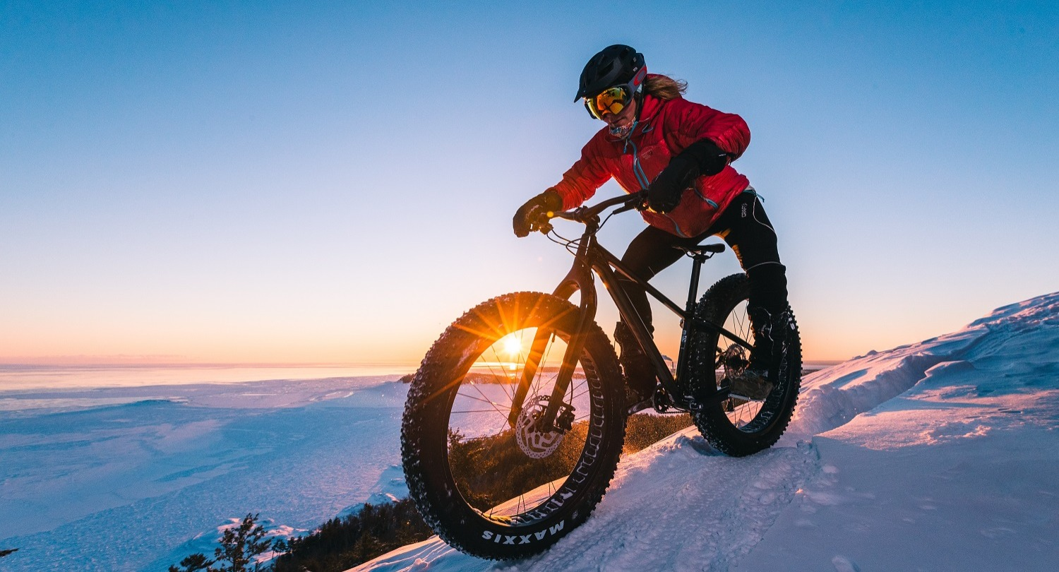 Person in red winter jacket riding a Giant Yukon fat bike down a gentle slope in winter with sunset in background
