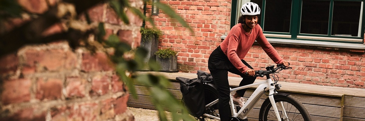 Woman wearing a white helmet riding a white ebike commuter with pannier bags and a rack through houses