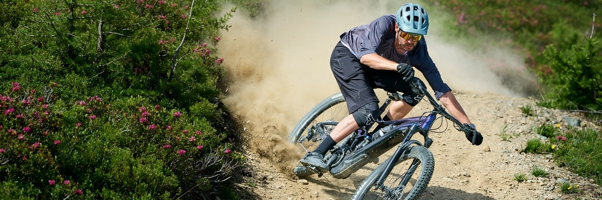 Man wearing helmet riding an e-mountain bike on a dusty mountain trail doing a skid