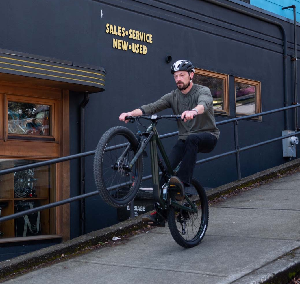 Gary TeGantvort wearing a helmet and riding a wheelie down the Lynn Street sidewalk next to the Mountlake Bicycle Shop.