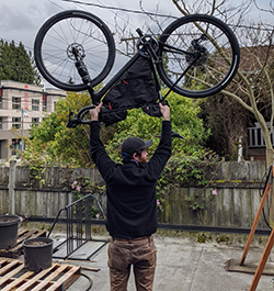 Bryce Kirk, on the roof of the Montlake Bicycle Shop holding a Sala Warbird over his head with a custom Boge Works frame bag.