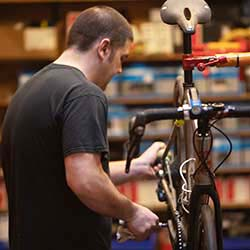"""Mike """"Turm"""" lubing the chain of a Lynskey on the Montlake Bicycle Shop sales floor."""