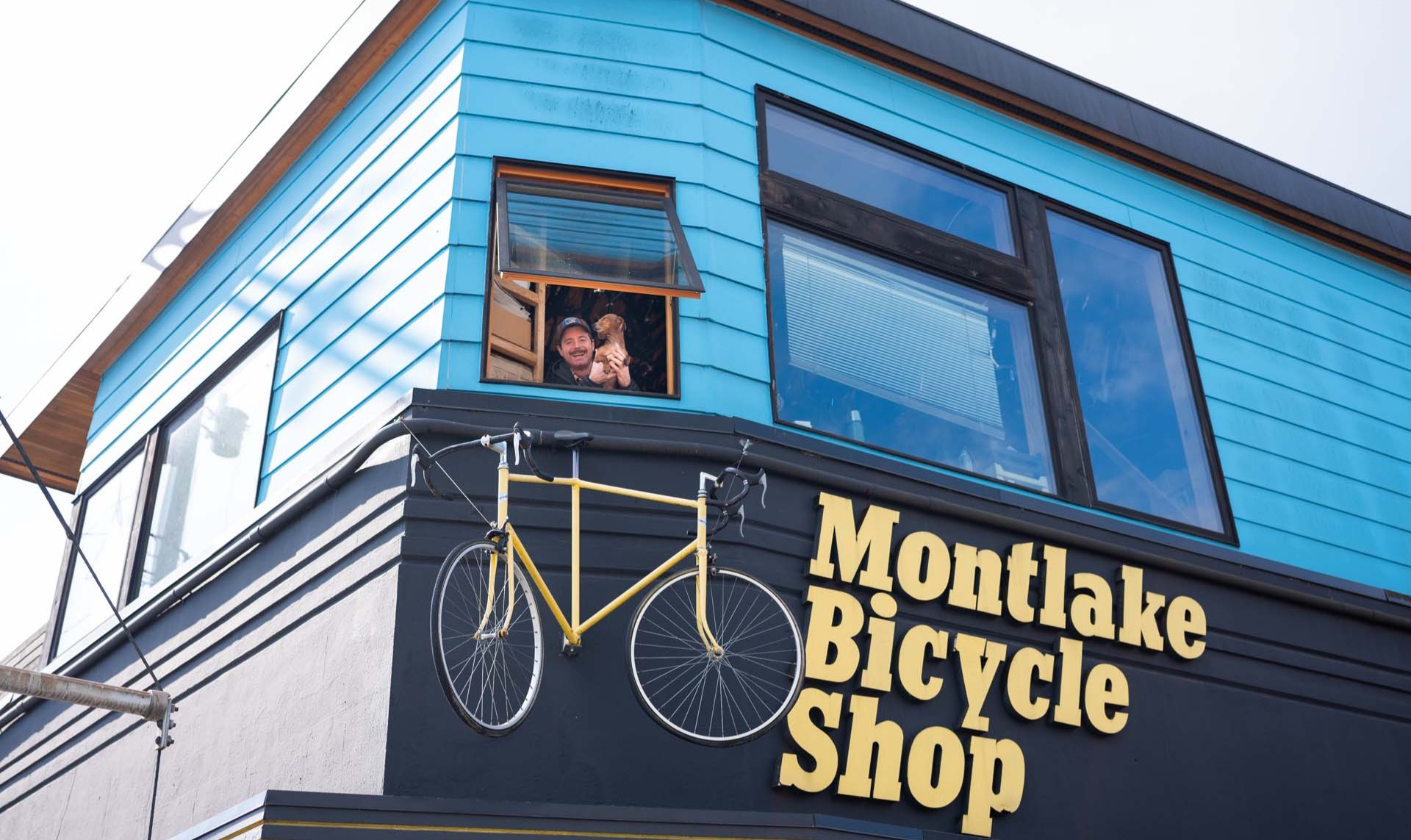 Photo of Patrick Montheith holding his Weiner dog Frankie out the front window the the Mountlake Bicycle Shop. Below the window is a double sided bike at the Montlake Bicycle Shop sign.
