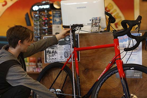 A member of the Montlake sales staff measuring the seat height of a road bike