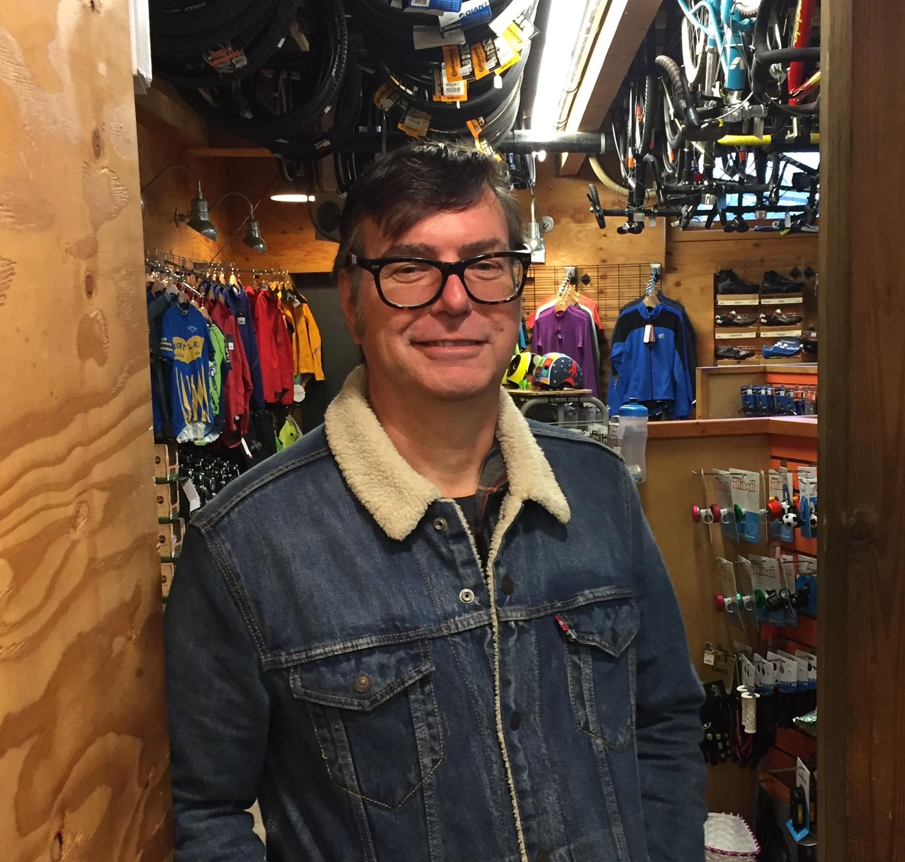 Brian Probart in on the sales floor looking handsome wearing a denim jacket and big square glasses