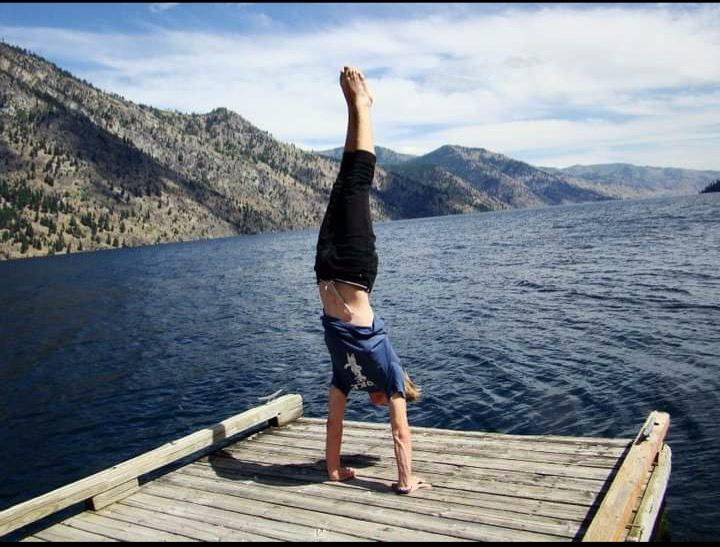 Devin Johnson doing a handstand on a dock in front of a large body of water on a sunny day. There is a rolling hillside in the background.