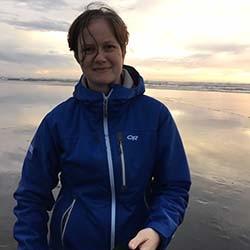 Carolyn Eaton wearing a purple winter coat at sunset on a WA coast beach.