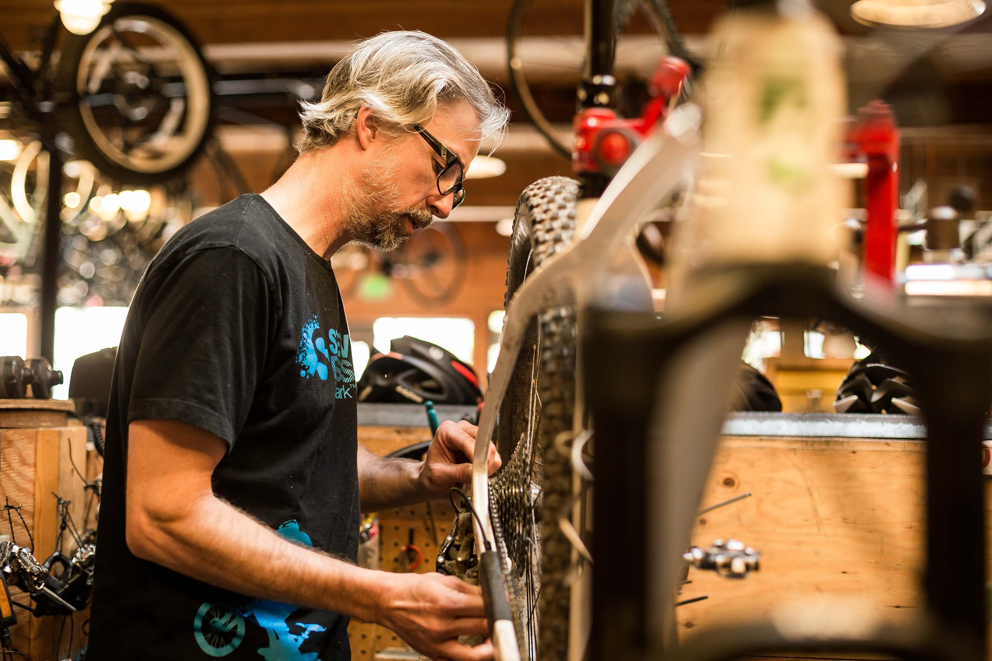 A mechanic on the Montlake Bicycle Shop sales floor working on a mountain bike by checking the chain wear.
