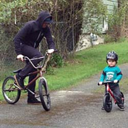 Adam Demer outside riding a BMX bike with a young boy next to him riding a scoot bike.