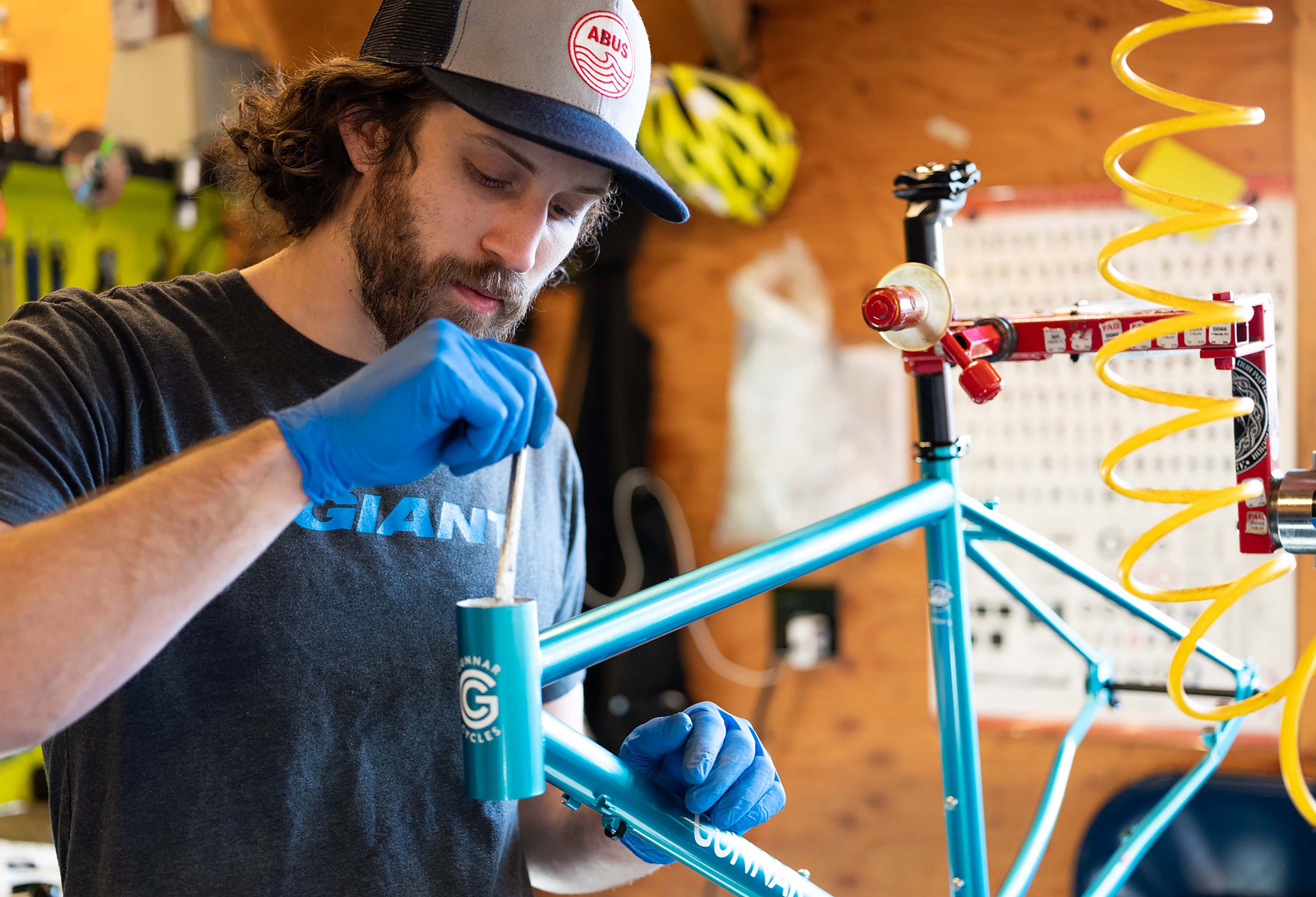 A mechanic greasing a head tube on a Gunnar Hyper XX in the Montlake Bicycle Shop service space.