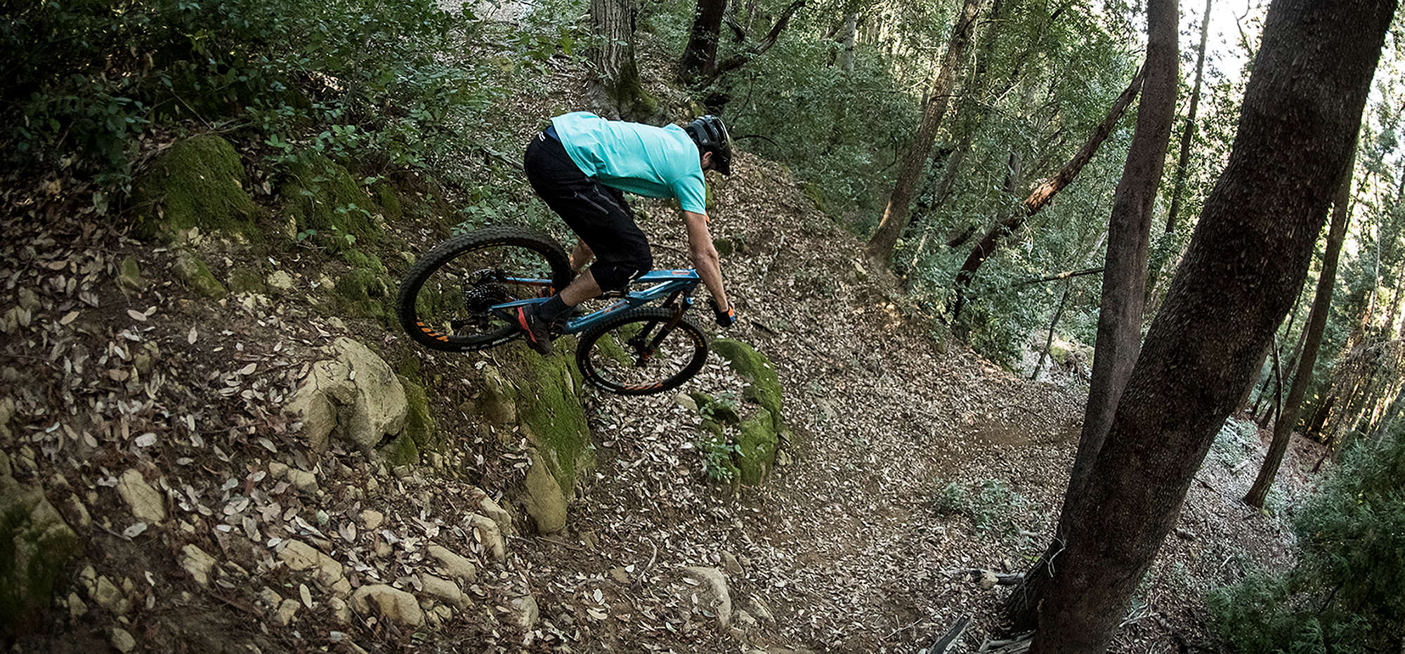 Man riding full suspension mountain bike over a difficult section of trail.