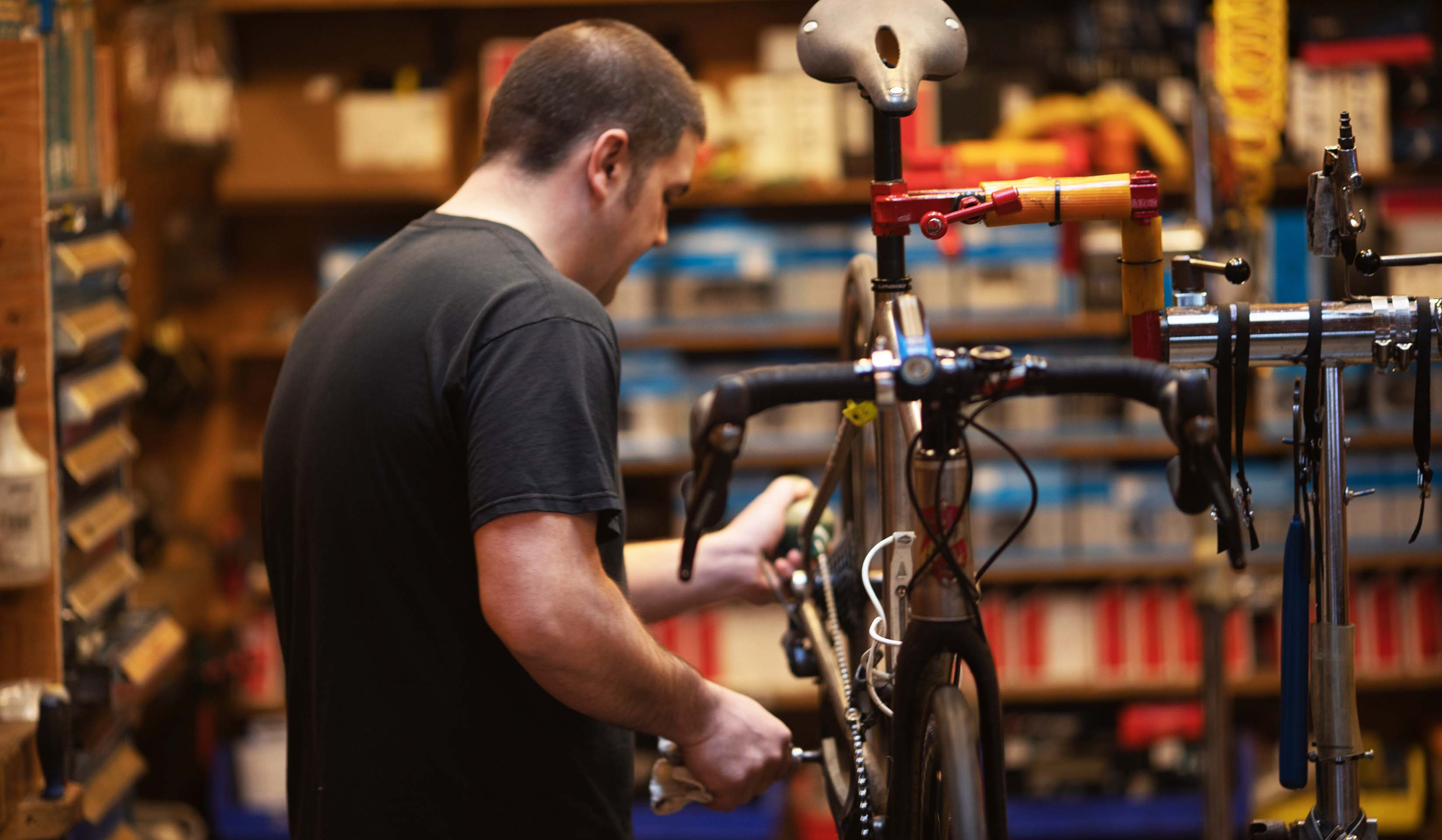Montlake Bicycle Shop employee lubing chain on a Lynskey road bike.