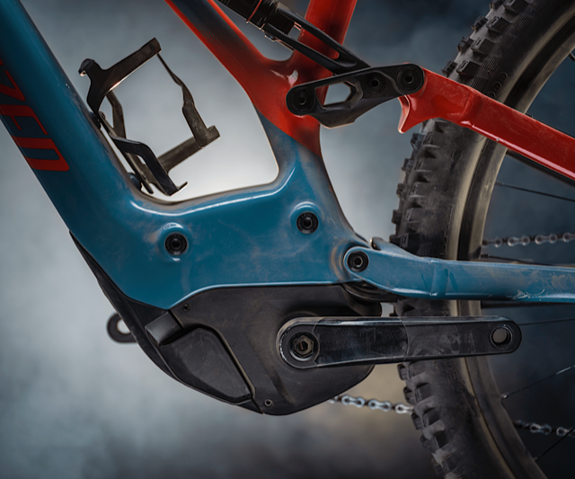 The motor of a red and blue Specialized Levo SL.