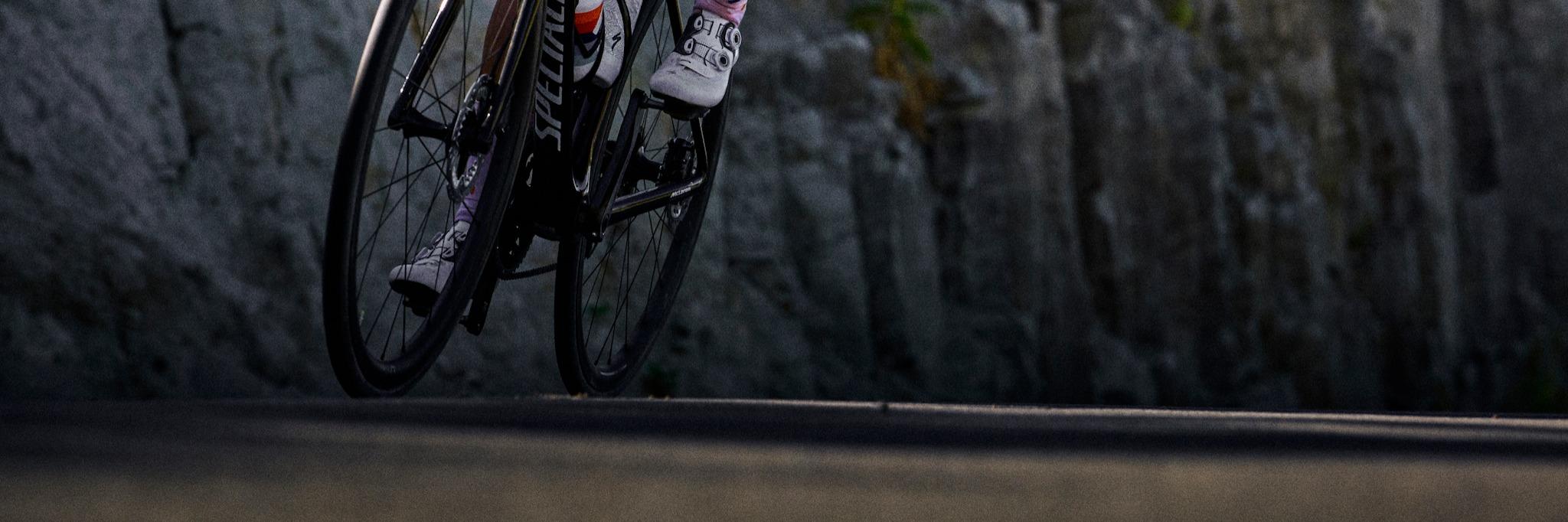 A person riding a Specialized Tarmac up a mountain with a rocky background.