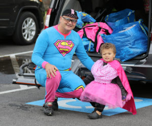 Father and daughter dressed in superhero costumes.