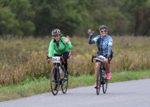Pair of road cyclists waving to the camera.