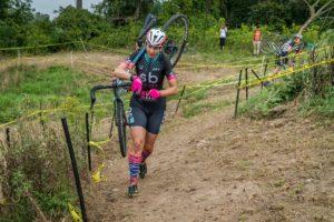 Cyclocross racer running up a hill.