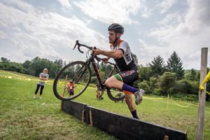 Cyclocross racer jumping over an obstacle.