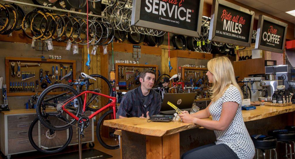 Customer talking to a Repair Technician about her bike repair.