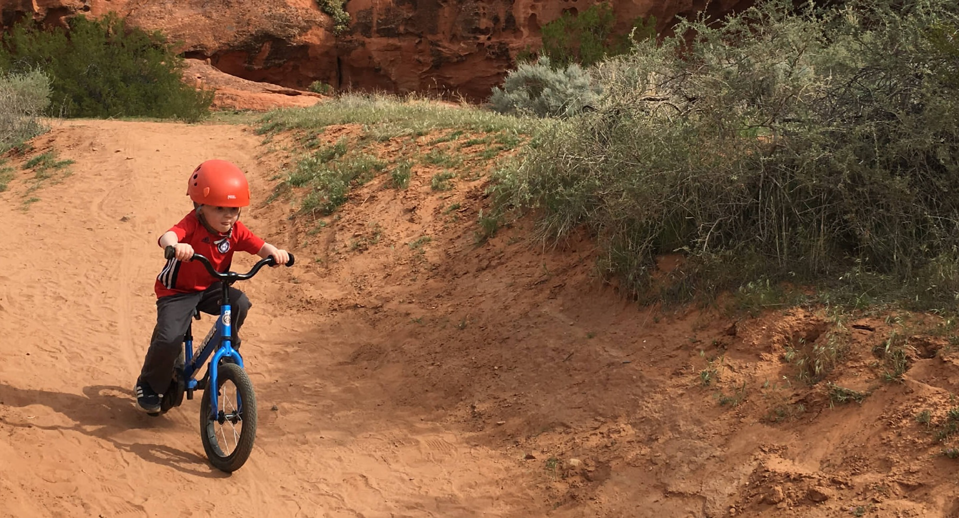 A young child coasts down a red dirt trail on a balance bike