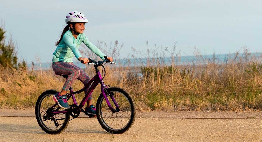 A child rides a bike across a beachfront pathway