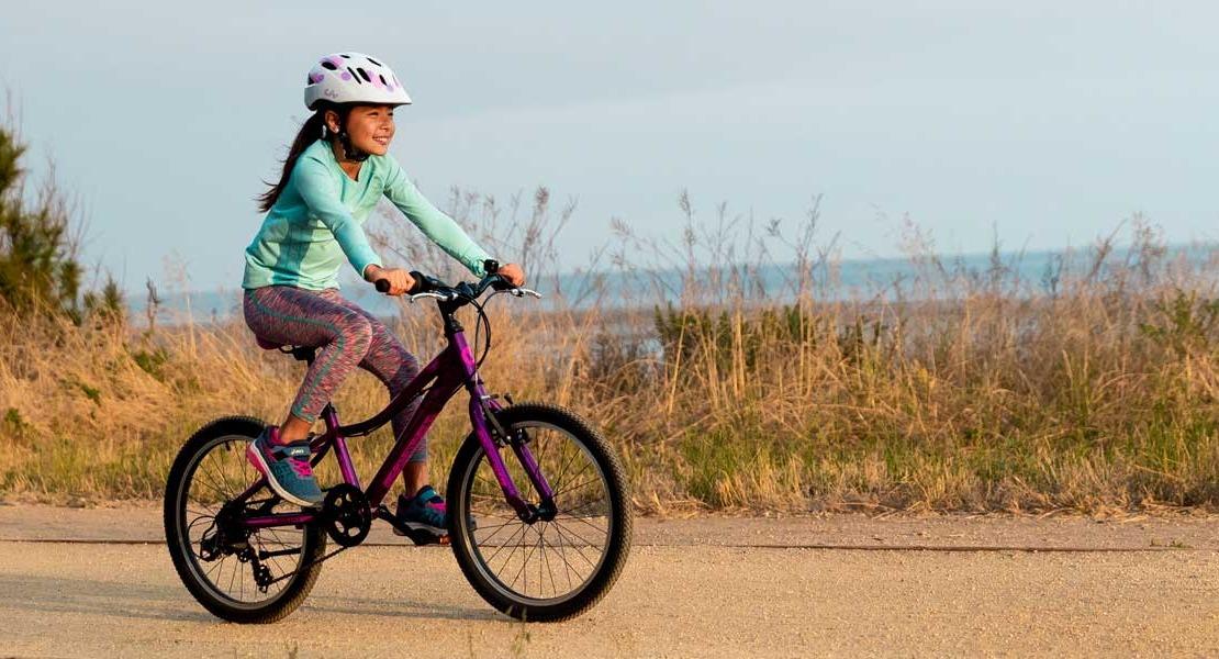A young cyclist rides a bike near the beach
