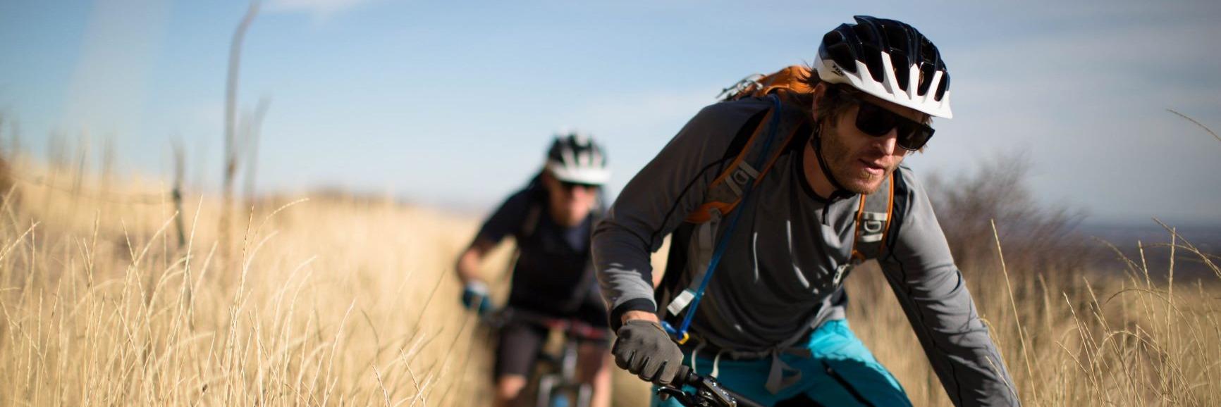 Mountain biker riders on a mountain meadow trail