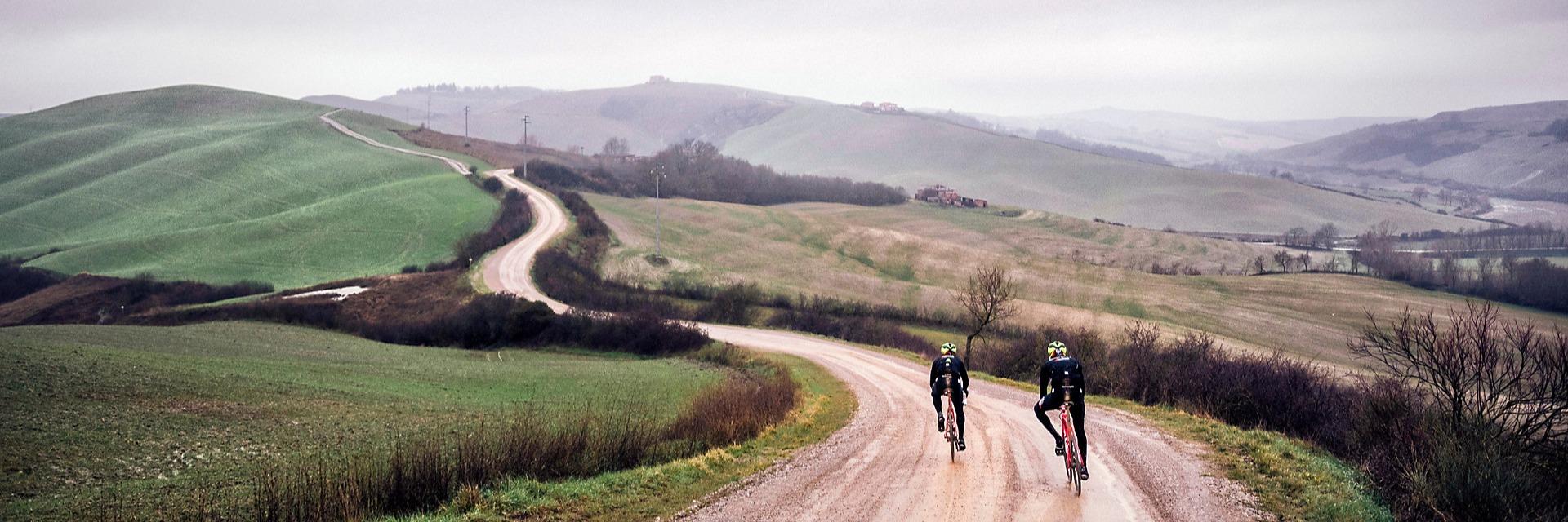 Cyclists ride Trek's Domane on a wet dirt road