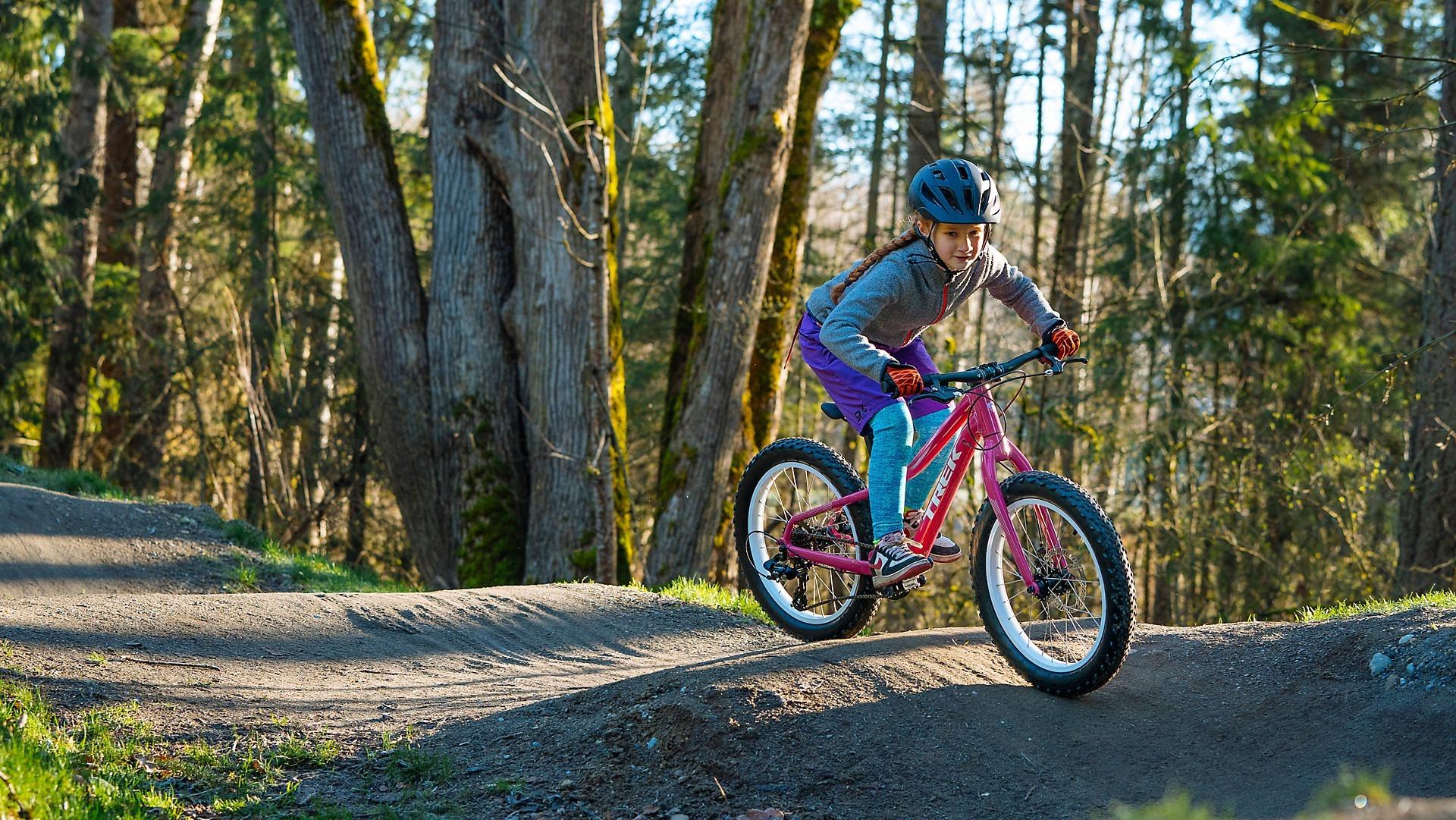 A child rides a kid's bike on a dirt trail