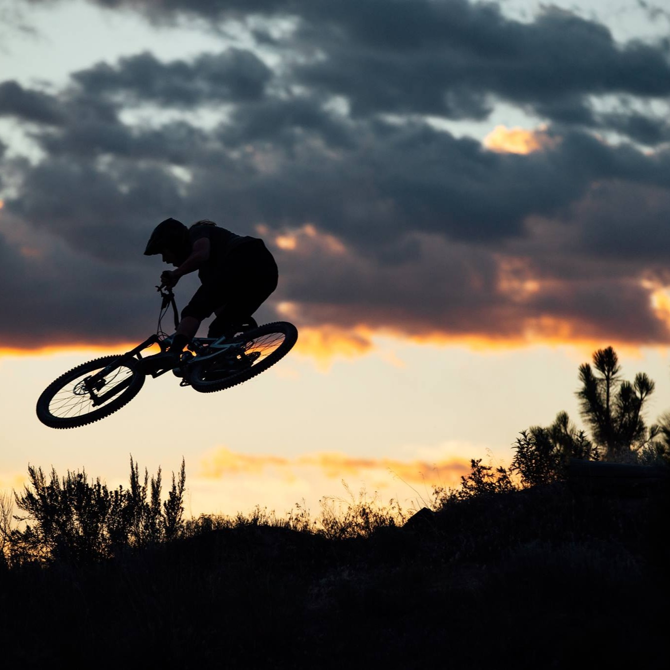 Mountain biker soars through a sunset sky