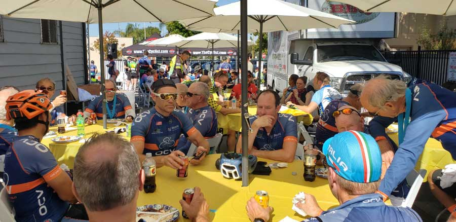 cyclists at table enjoying refreshments after charity ride