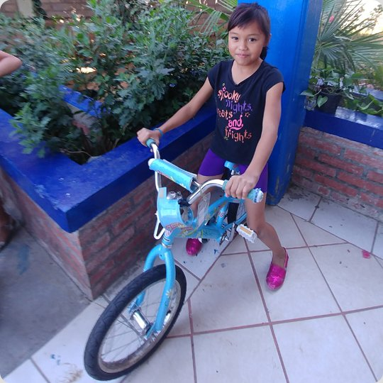 little girl on blue bike