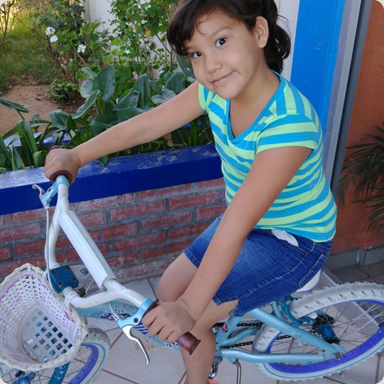 little girl on blue bike with basket